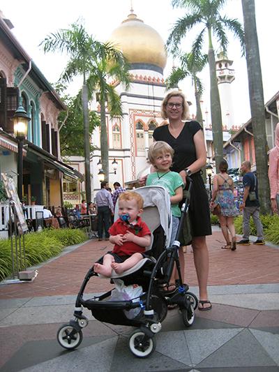 Ett barn i barnvagn, ett på ståbräda och en vuxen bakom.