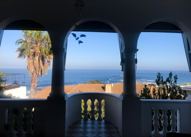 Utsikt från balkong. Hav och palm.