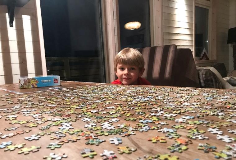 Ett barn vid ett bord fullt med pusselbitar.