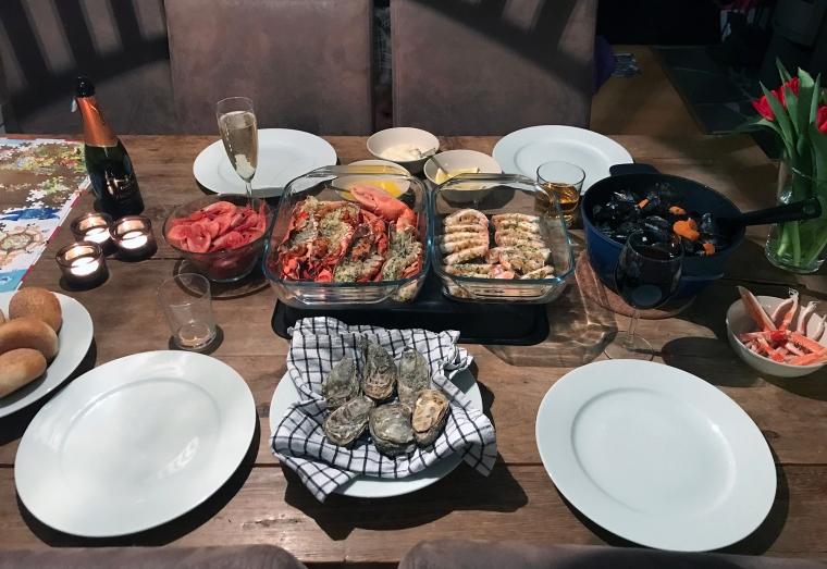 Ett dukat bord med flera sorters skaldjur.