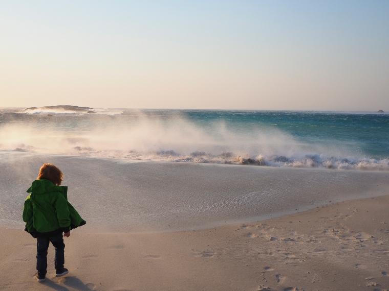 Ett barn i blåsten på stranden.
