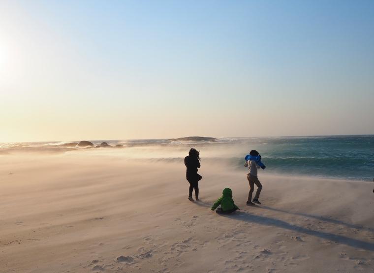 Tre barn som står i blåsten på stranden i Camps bay