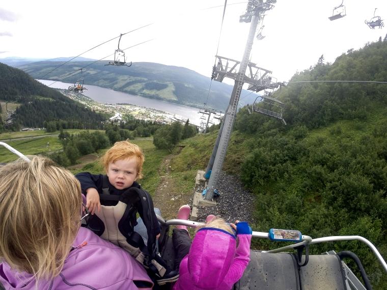En vuxen och två barn i en sittlift i fjällen på sommaren.