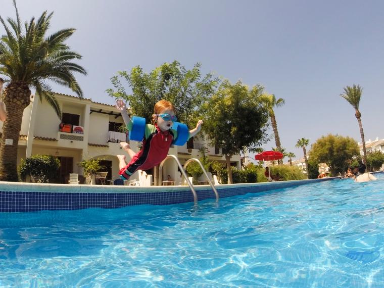 Barn som slänger sig i en pool.