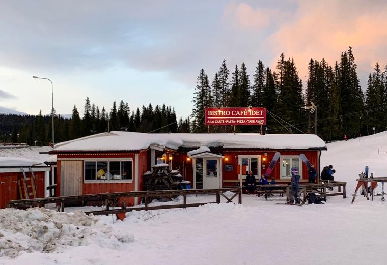 Ett rött trähus med en skylt på taket: Bistro Café Idet.