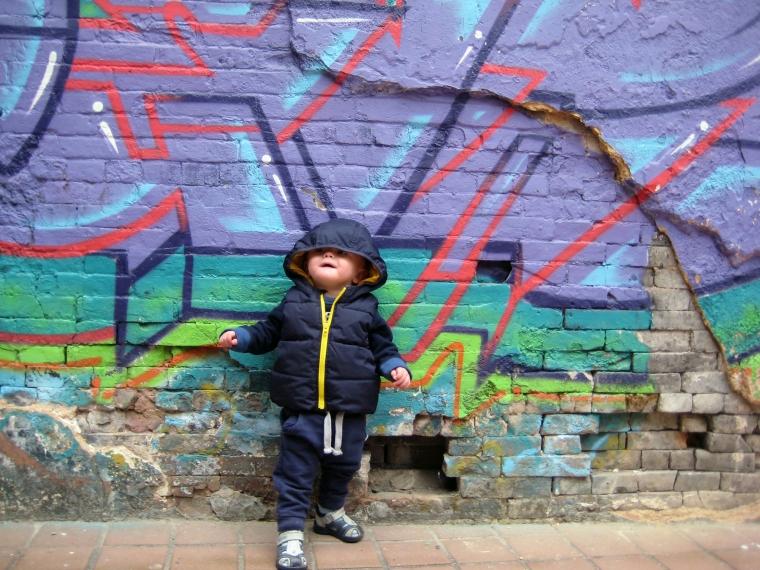 Barn framför en grafittivägg.