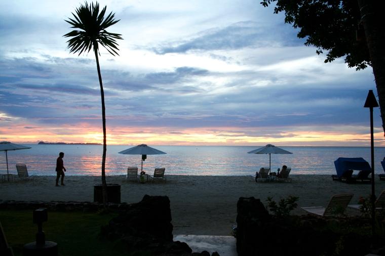 Solnedgång över strand och hav. Ett par solstolar och en palm i förgrunden.