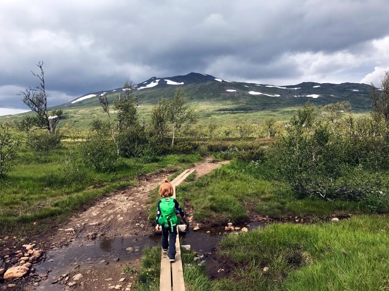 Barn med ryggsäck och fjäll i bakgrunden.