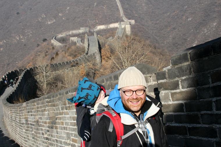 Man med barn i bärstol på Kinesiska muren.