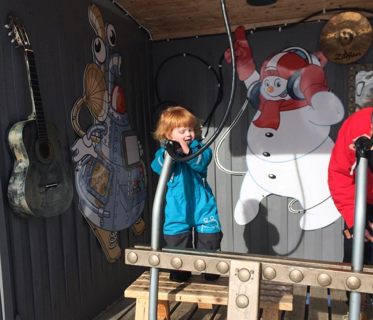 Barn som sjunger i en leksaksmikrofon.