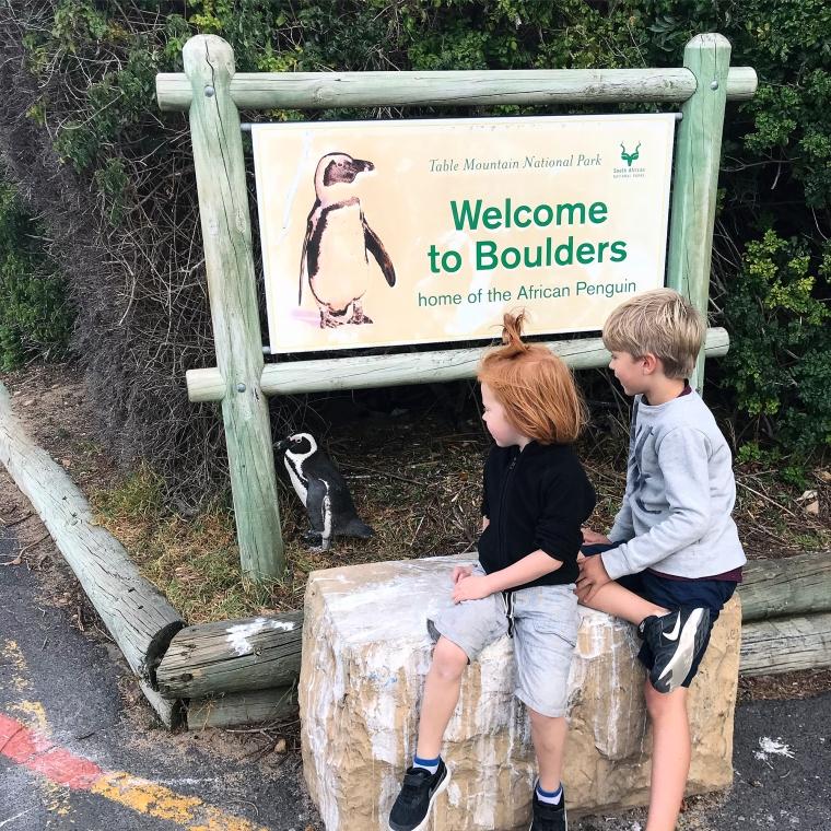 Två barn, en välkomstskylt och en pingvin.