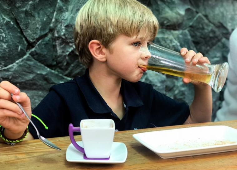 Ett barn som dricker gul vätska ur ett ölglas och har en espressokopp framför sig.