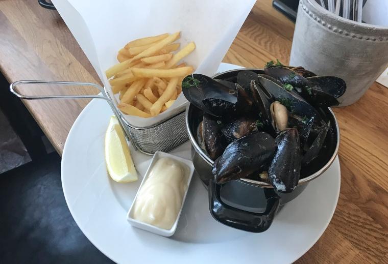 En tallrik med musslor och pommes.