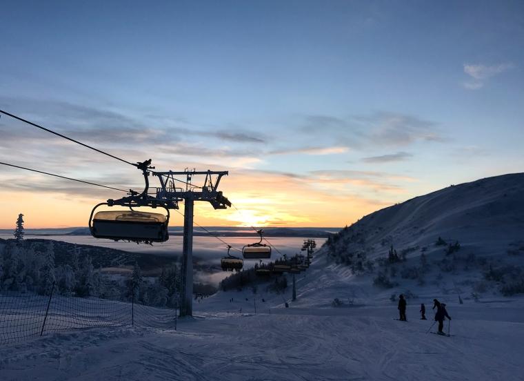 Skidbacke med sittlift och soluppgång i bakgrunden.