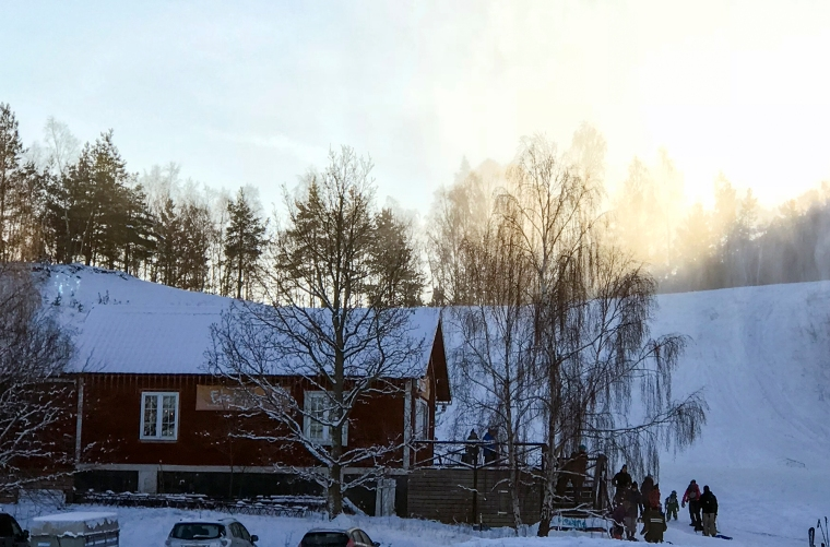 Rött hus med terrass precis i slalombacke.