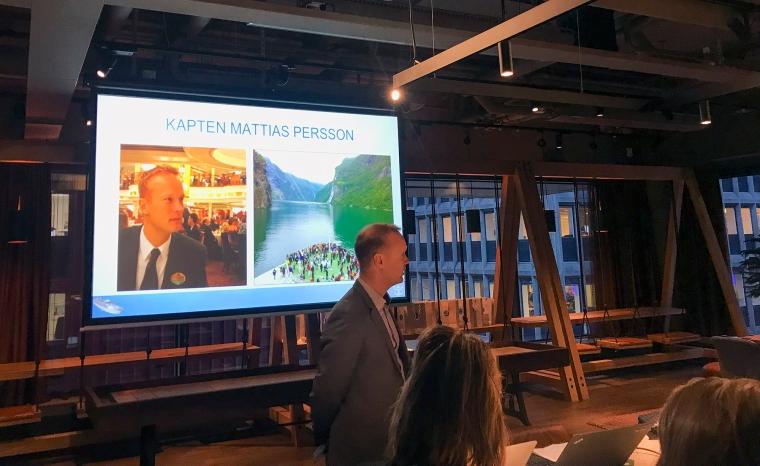 En man framför en presentation. Den skymtas också publik. På presentationen står mannens namn Kapten Mattias Persson.
