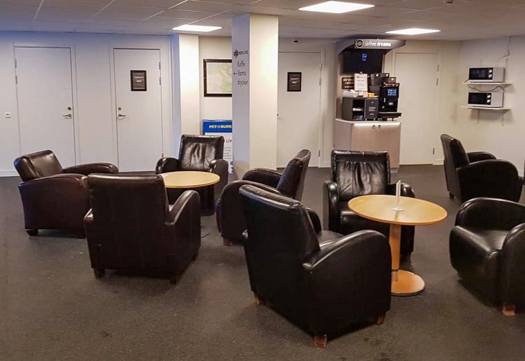 Ett rum med bruna fotöljer och träbord i små grupper.