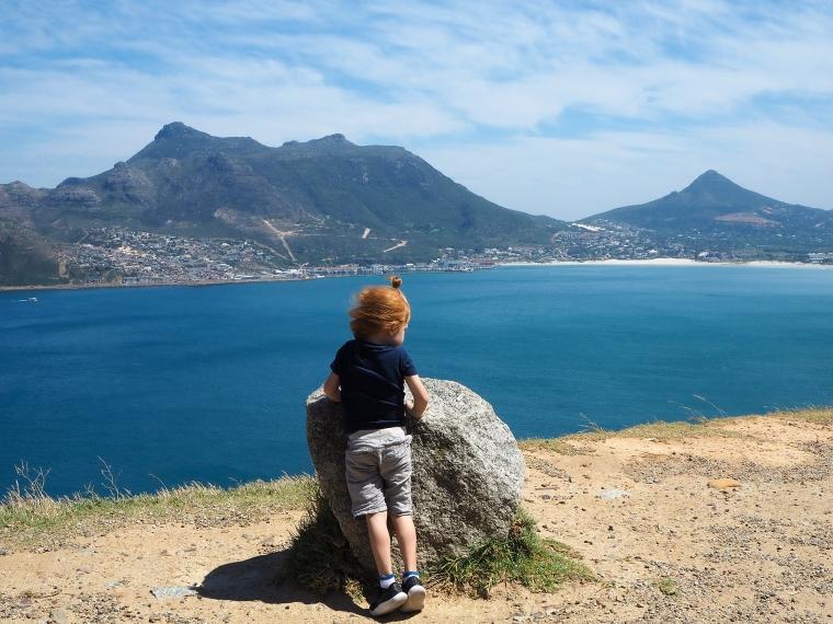Ett barn vid en sten med utsikt över en vik med berg i bakgrunden.