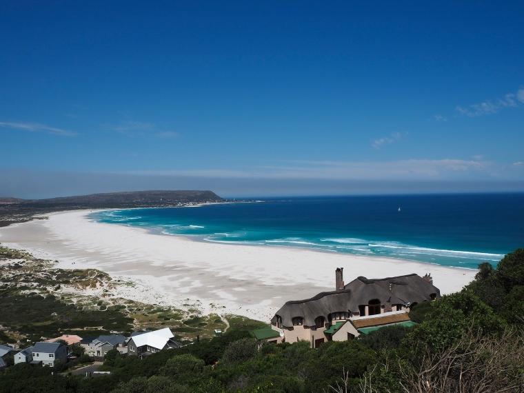 En vit sandstrand och ett lysande blått hav.