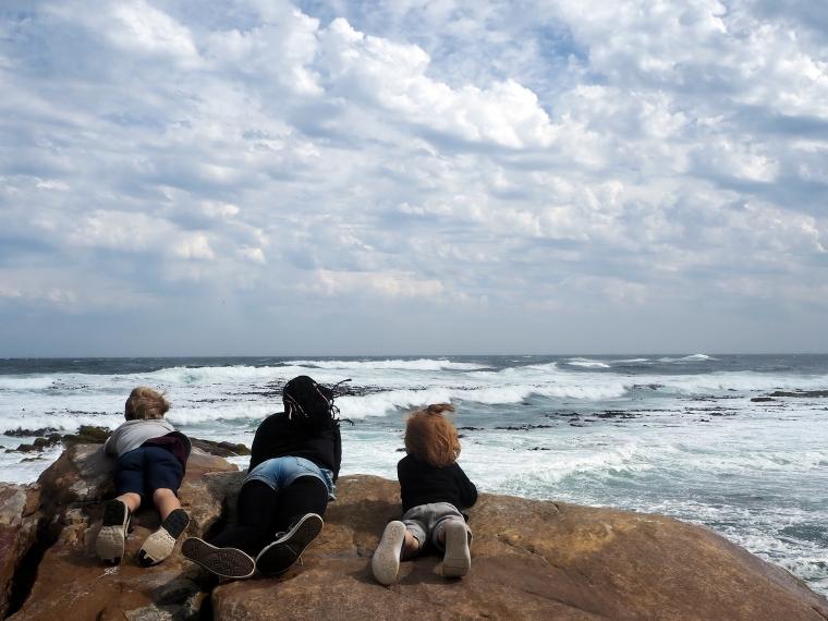 Tre barn som spanar på havet.