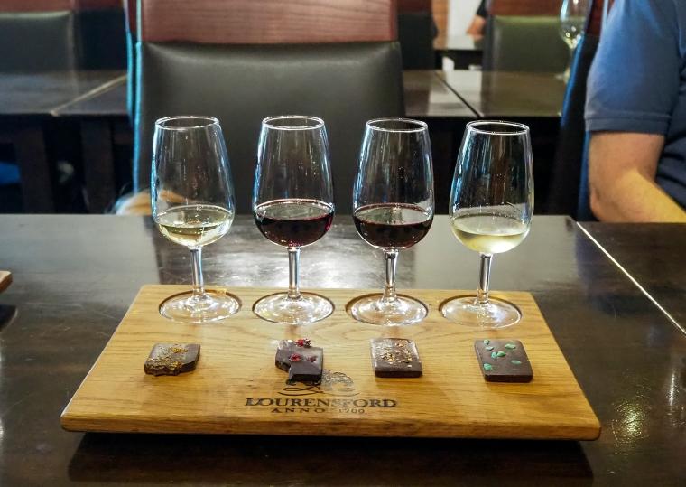 En träbricka med fyra vinglas. Två med röd vätska och två med gul vätska. Framför glasen ligger fyra chokladbitar med olika smak.