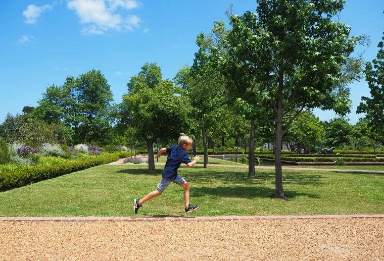 Ett barn som springer på en gant av tegel mellan en gräsmatt och en grusgång.