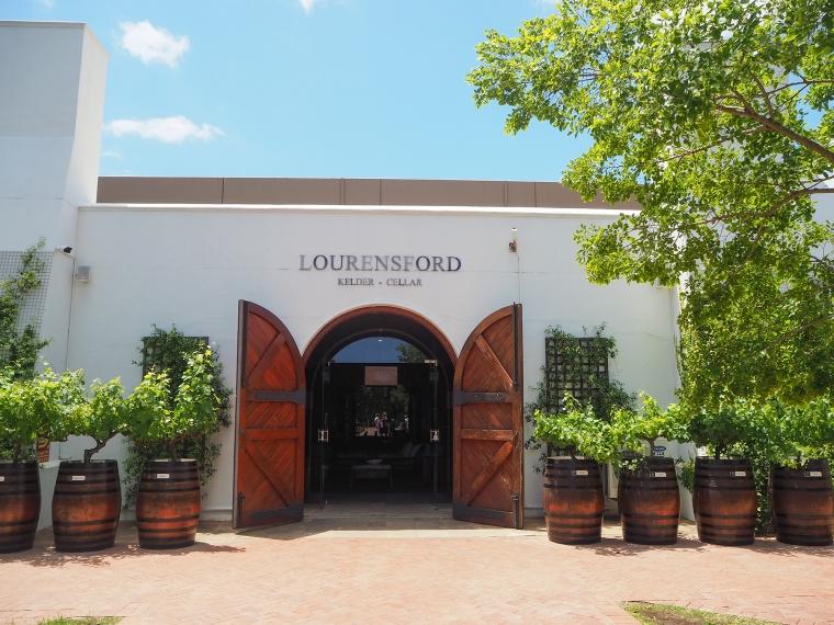 Vitt hus med en stpr dubbeldörr. Text ovanför dörren: Lourensford, Kelder, Cellar. Vinrankor i vintynnor på båda sidorna om dörren.