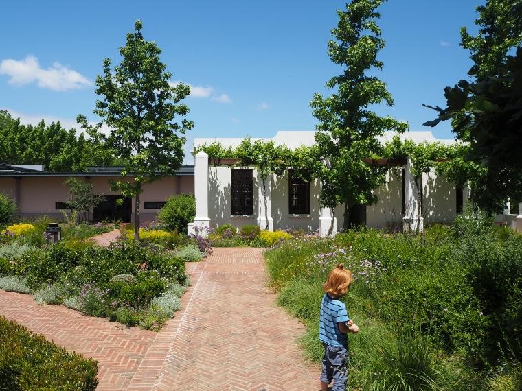 en grönskande park/trädgård med en vit byggnad i bakgrunden och ett barn i förgrunden.