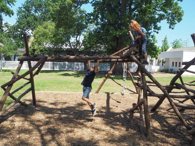 Två barn som klättrar i en klätterställning av trädstockar.