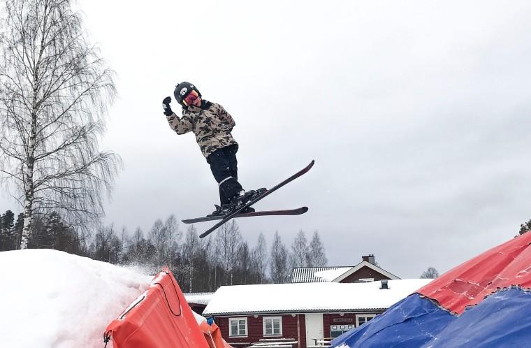 Barn på slalomskidor som gör ett hopp.