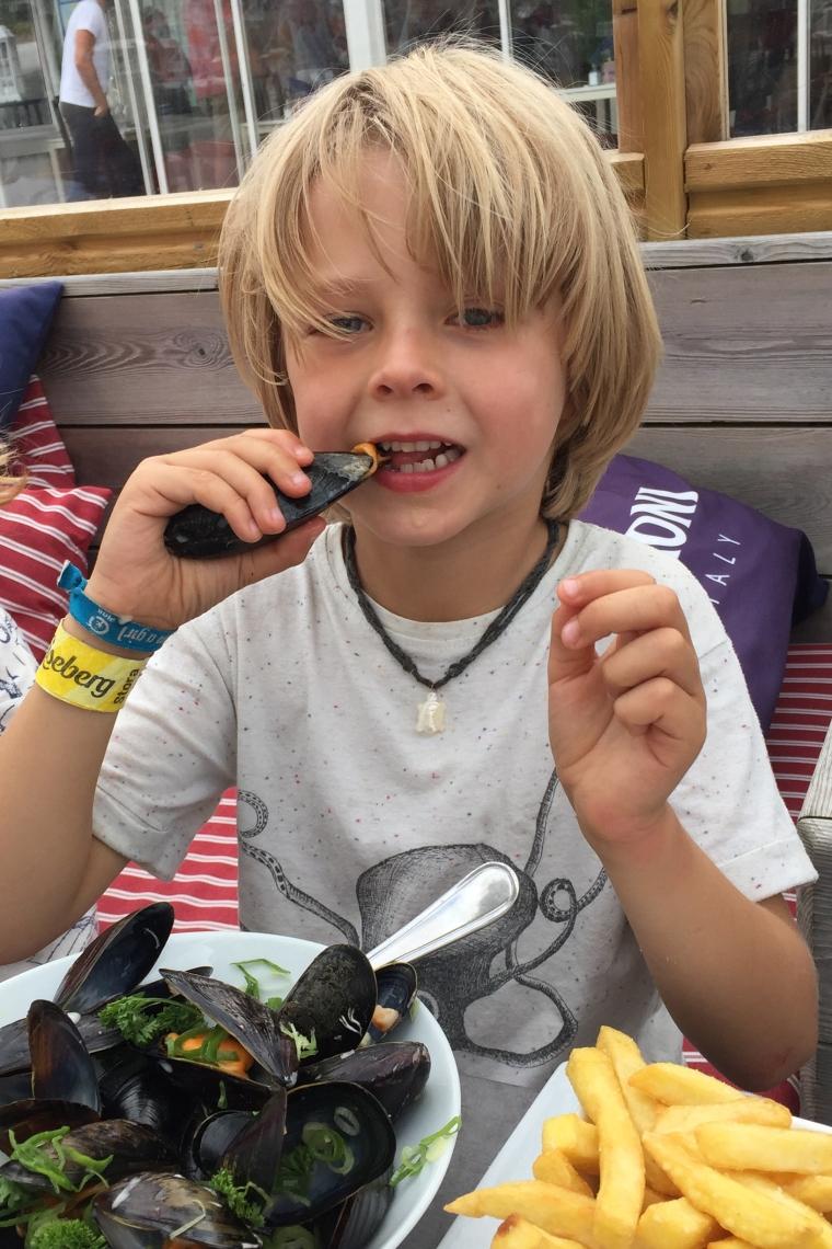 Ett barn som äter musslor.