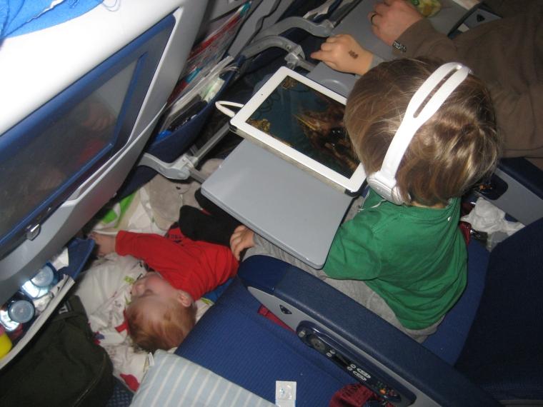 Två barn på ett flyg. Ett sover på golvet och ett tittar på iPad.