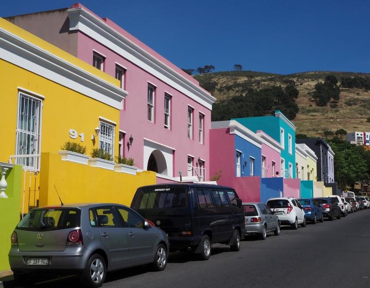 En gata med parkerade bilar och färgglada hus – grönt, gult, rosa, blått, rosa. tukost, vitt, gult grått och lila.