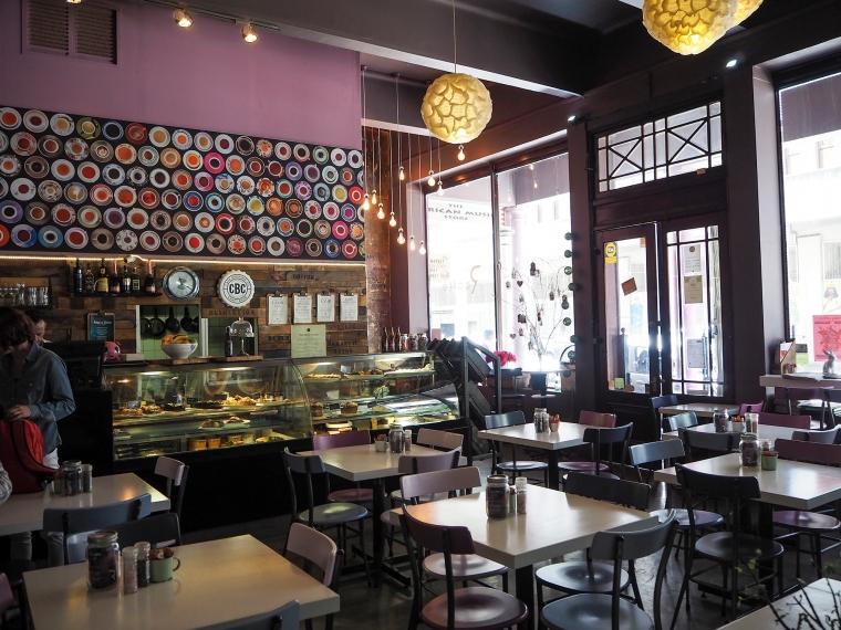 Översikts bild inne ifrån ett caffé. Kvadratiska bord med stolar. Lila väggar.