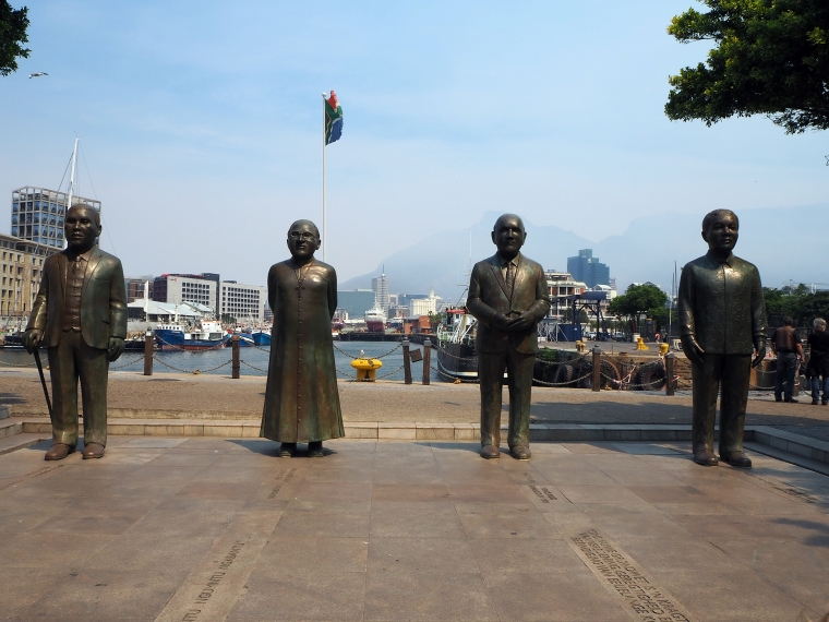 Fyra statyer av män. Hamn i bakgrunden.