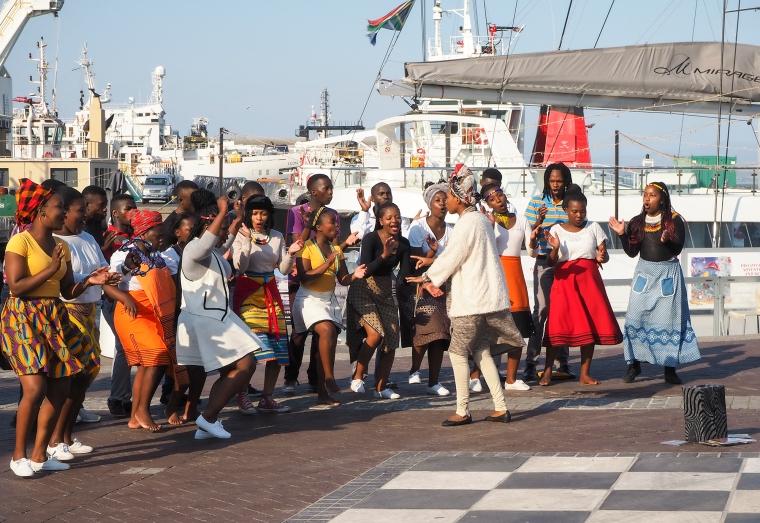 En grupp sjungande människor i färgglada kläder.