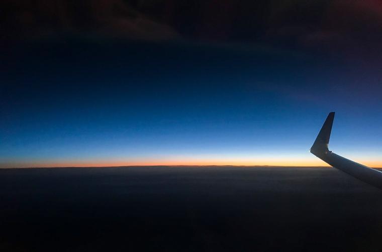 Stimma ljus på en mörk himmel och mörka moln. En flygplansvinge skymtar.