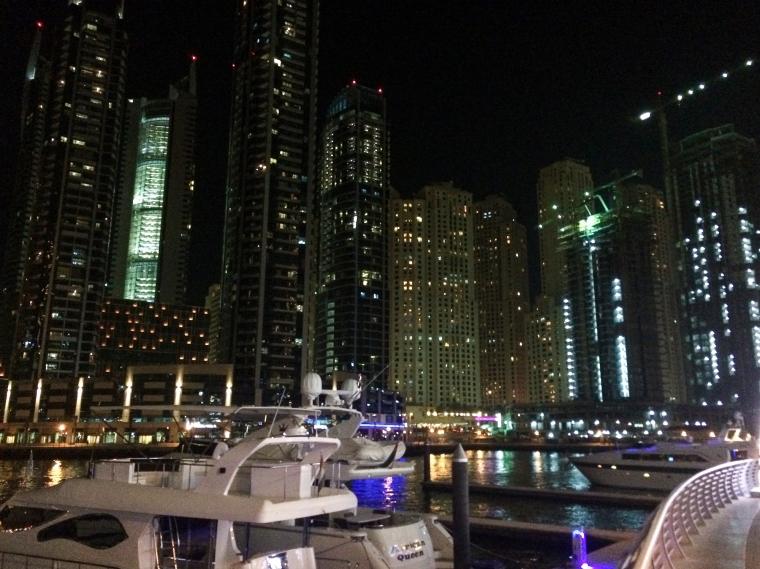 Kvällsbild från en marina med skyskrapor i bakgrunden.