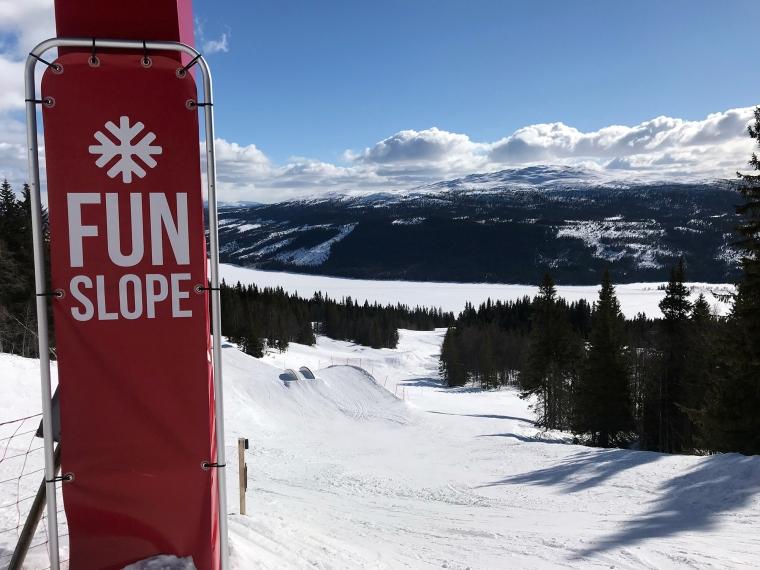 Skylt med texten: Fun slope. Slalombacke i bakgrunden.