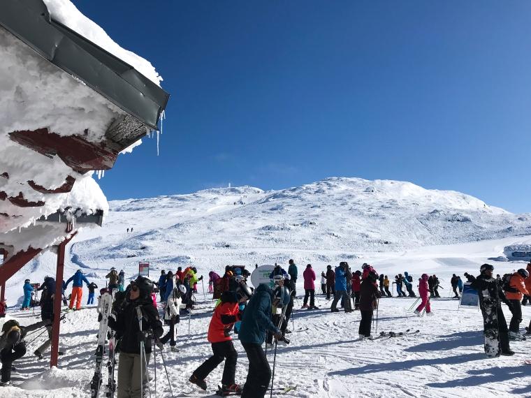 Massor av skidåkare och en fjälltopp i bakgrunden.