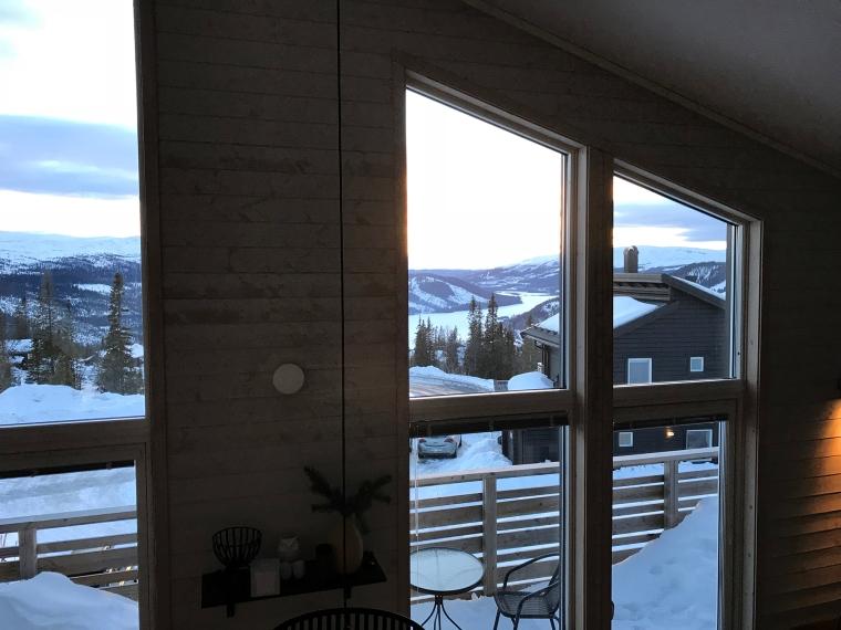 Korttaget ut genom fönster med utsikt över fjäll och sjö.