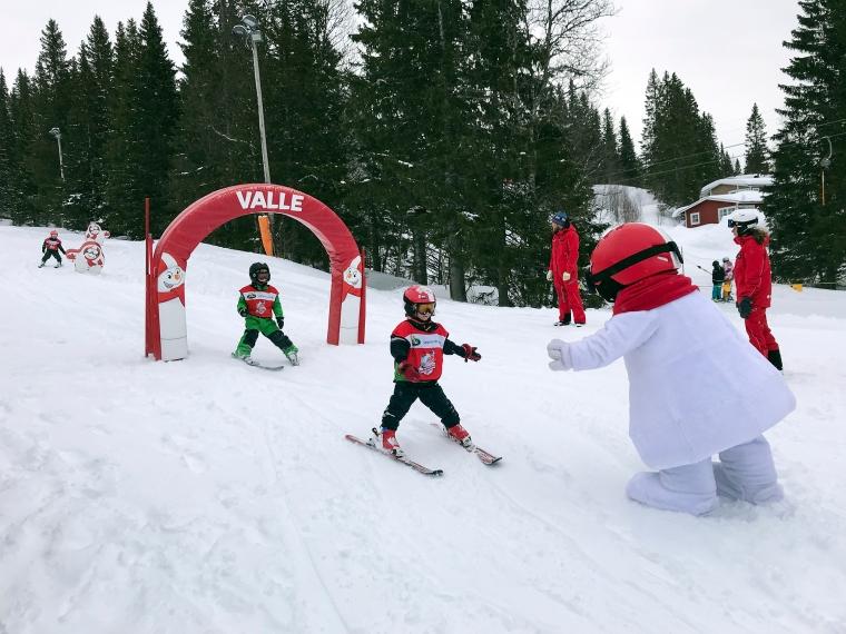 Utklädd snögubbe och barn som gör high five.