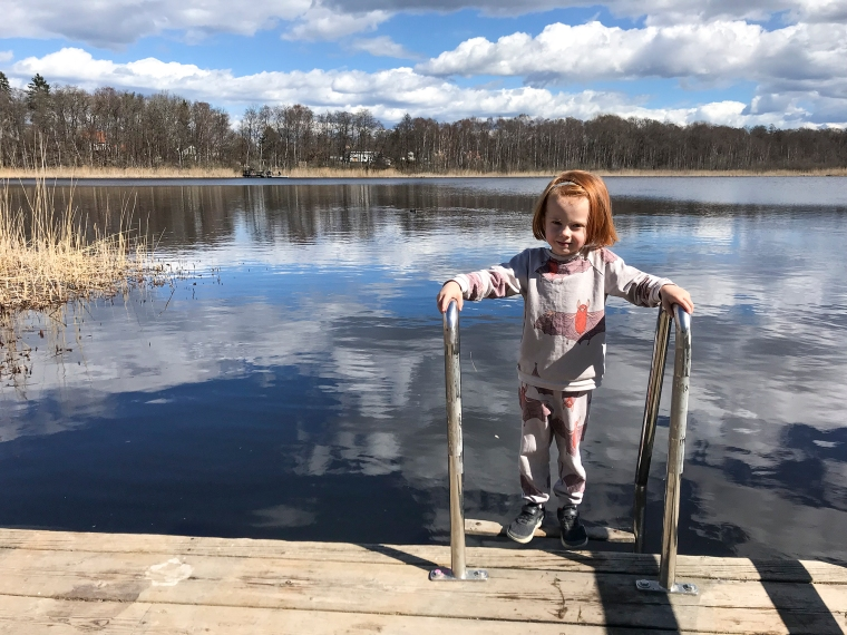 Barn på en brygga med en sjö i bakgrunden