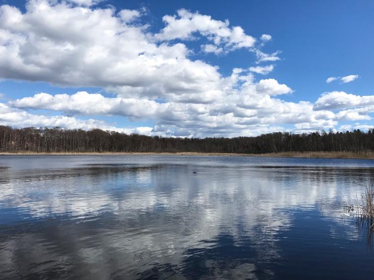En sjö där molnen på himlen speglar sig