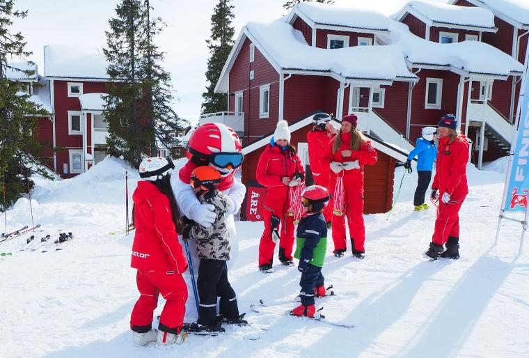 Utklädd snögubbe kramar om barn.