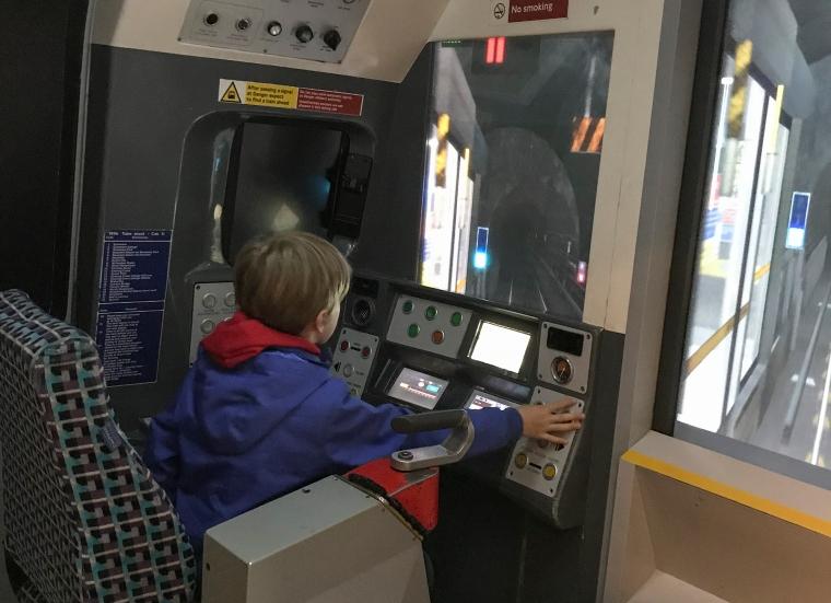 Ett barn sitter och kör en modell av ett tunnelbanetåg.