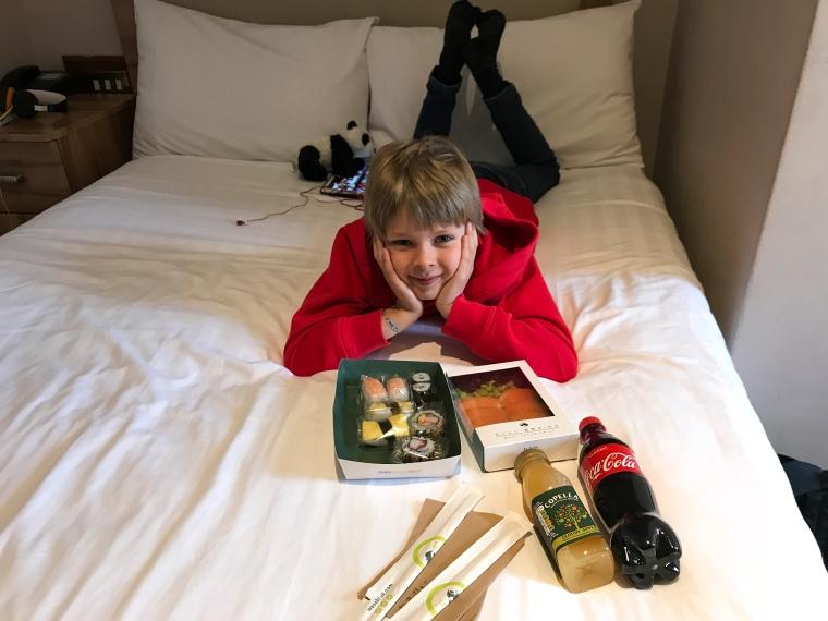 Ett barn ligger på mage på sängen med två sushilådor och två drickor framför sig.
