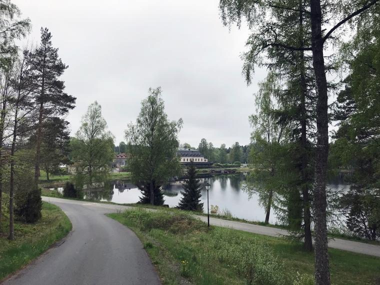 Träd i förgrunden, en spegelblank sjö och en gul herrgård i bakgrunden.