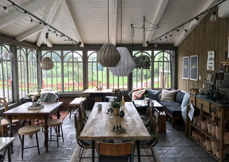 Inifrån ett orangeri med bord och stolar för fikagäster.