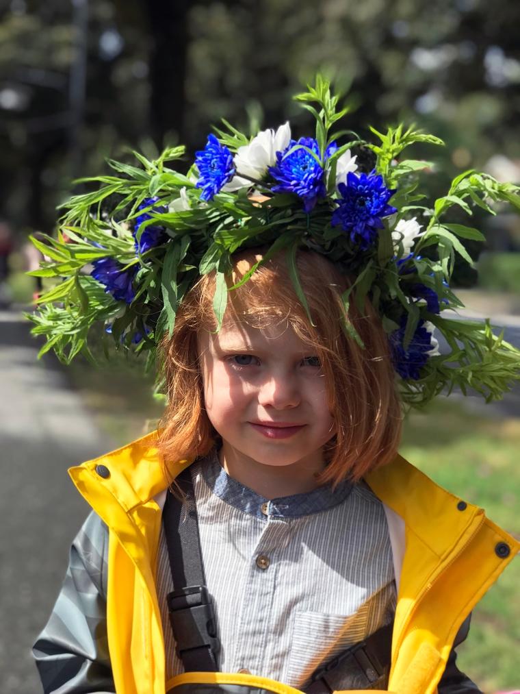 Ett barn med gallonställ och blomsterkrans i håret.